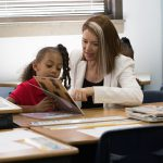 Deborah Gist sits and reads with a student in a Tulsa school classroom