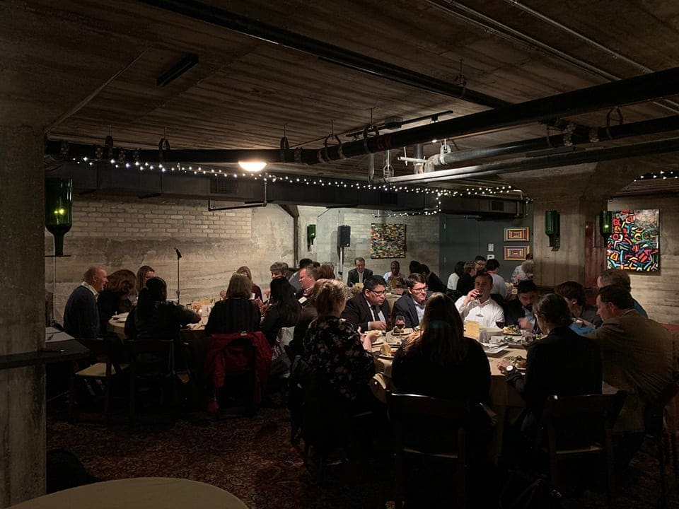 Group of people sitting at tables at Civil Discourse Dinner at SXSW EDU